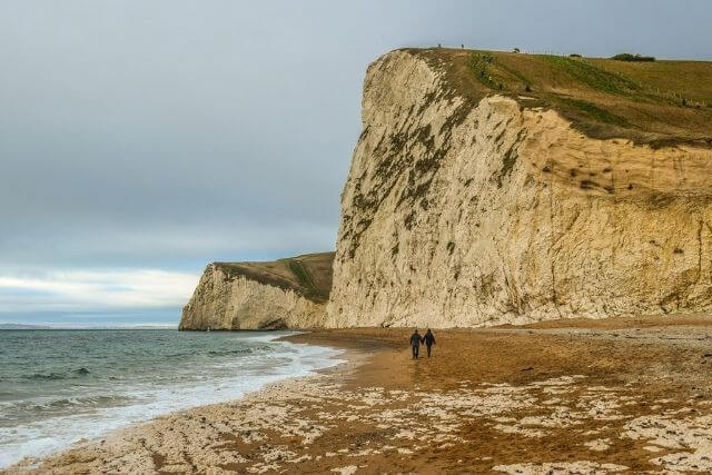 Two people walking hand in hand along the Jurassic Coast